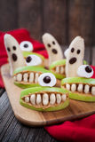 Spooky halloween edible monsters scary food. Healthy vegetarian snack dessert recipe for party decoration. Homemade cyclop apples with teeth and banana ghosts Stock Image