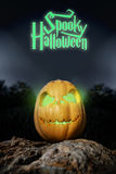 Spooky Halloween neon pumpkin in on a rock in the darkness Royalty Free Stock Photo