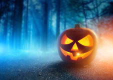 Spooky Halloween Night. A glowing Jack O Lantern in adark mist Forest on Halloween