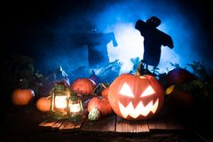 Spooky Halloween pumpkin with blue mist and scarecrows. On dark background Royalty Free Stock Photography
