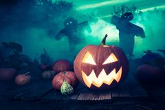 Spooky Halloween pumpkin on dark field with scarecrows Royalty Free Stock Photo