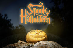 Spooky Halloween warm neon pumpkin in on a rock in the darkness Royalty Free Stock Photography