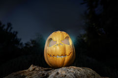 Spooky Halloween warm neon pumpkin in on a rock in the darkness Royalty Free Stock Photos