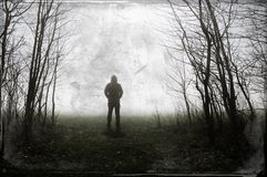 A spooky hooded figure standing on the edge of woodland. On a foggy winters night. With a grunge, retro edit.  stock photography