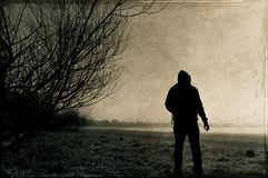A spooky lone hooded figure. Standing on the edge of a field on a cold, misty winters night. With a sepia, grunge, vintage edit.  stock photo