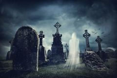 Spooky old graveyard and a ghost. At night Royalty Free Stock Photos