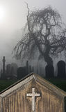 Spooky old headstone in a foggy graveyard Royalty Free Stock Photography