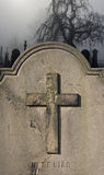 Spooky old headstone in a foggy graveyard Stock Image