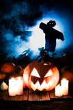 Spooky pumpkin on dark field with scarecrows for Halloween Royalty Free Stock Photos