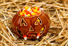 Spooky pumpkin filled with candy corn on straw Stock Photography
