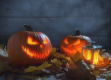 Spooky pumpkins jack o lantern among dried leaves on wooden fence Stock Photo
