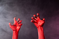 Spooky red devil hands with black glossy nails Stock Photo