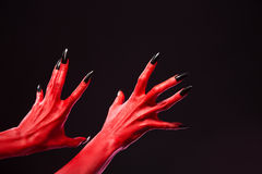 Spooky red devil hands with black nails, real body-art. Spooky red devil hands with black nails, Halloween theme, studio shot on black background Royalty Free Stock Photography