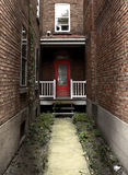 Spooky red door surrounded by brick walls Royalty Free Stock Image