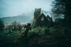 Spooky ruined church surrounded by a graveyard on a misty winters day in the English countryside royalty free stock image