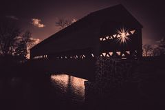 Spooky Sachs covered bridge in Gettysburg, PA in silhouette with a sunburst royalty free stock image