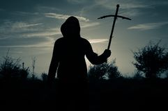 A spooky silhouette of a hooded man standing outside holding a wooden homemade cross at sunset. With a vintage grainy edit.  royalty free stock image