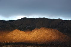 Spooky Sunlight at Sunset on the Sandia Mountains. Mountain at sunset has light coming from behind it Royalty Free Stock Photos