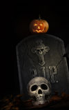 Spooky tombstone with skull and pumpkin on black Royalty Free Stock Images
