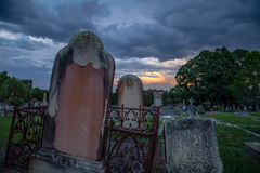 Spooky Twilight Storm at Old Cemetery with Leaning Tombstones Stock Photos