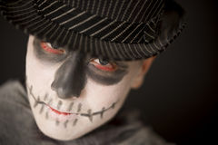 Spooky young man in Halloween costume. Wearing skull makeup and a dark hat and cloak looking up at the camera with red rimmed eyes, close up of his face Royalty Free Stock Photo