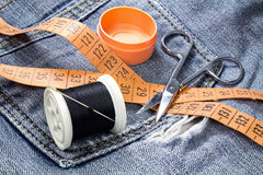 Spool of black thread with a needle, tailor`s tape measure and scissors on a background of denim Stock Image