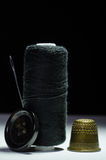 Spool of black thread with a needle, thimble, button Stock Images