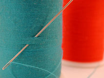 Spool of blue thread with needle. Threaded needle in spool of blue thread with spool of red thread in the background stock image