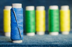 Spool of blue thread with a needle on the background of spools of green and yellow threads on a denim fabric stock photography