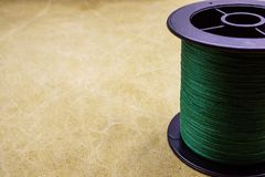 Spool of cord on the background of tarpaulin. Green fishing line. Spool of braided fishing line. Spool of cord on the background of tarpaulin. Green fishing line royalty free stock images