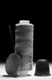 Spool of gray thread with needle thimble and button Royalty Free Stock Images