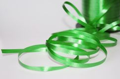 Spool of green curling ribbon on a white background Royalty Free Stock Photo