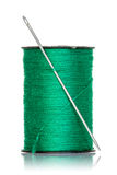 Spool of green thread with needle Stock Images