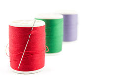 Spool of green thread and needle Royalty Free Stock Images