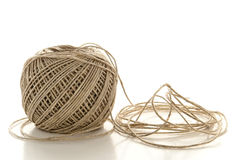 Spool of Natural Fiber Twine String over White. Spool ball of natural fiber brown twine made of light jute string strands with loose end over white Royalty Free Stock Image
