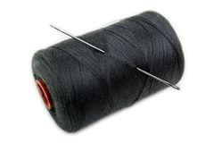Spool and needle. Sharp needle in sewing craft cotton thread spool Stock Photo