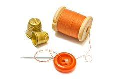 Spool of orange thread, and thimbles Stock Images