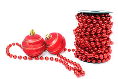 Spool of red beads and two christmas balls Stock Image