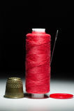 Spool of red thread with a needle thimble Royalty Free Stock Photos