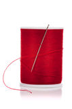 Spool of red thread and needle on white Stock Photos