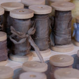 Spool with silk ribbons. Wooden spool with gray silk ribbons Stock Photo