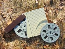 Spool of Super 8 film with cover laying in straw. With brown leaves Stock Image