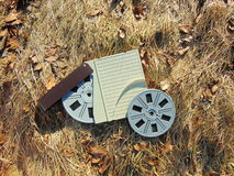 Spool of Super 8 film with cover laying in straw. With brown leaves Royalty Free Stock Photo