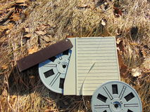 Spool of Super 8 film with cover laying in straw. With brown leaves Royalty Free Stock Images