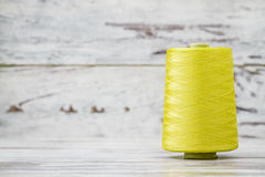 Spool of Synthetic Green Thread on White Wooden Background Royalty Free Stock Photo