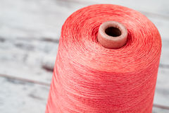 Spool of Synthetic Pink Thread on White Wooden Background Stock Photography