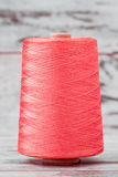 Spool of Synthetic Pink Thread on White Wooden Background Royalty Free Stock Images