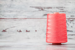 Spool of Synthetic Pink Thread on White Wooden Background Stock Image