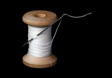 Spool of thread. Needl in spool of thread on black Stock Image