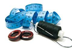 Spool of thread, buttons and meter on white Stock Images